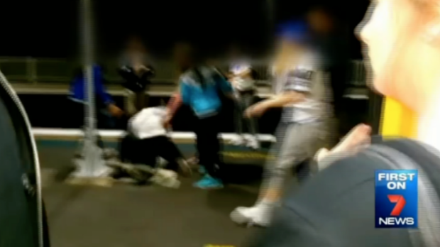 The brawl between a group of teenage girls, which started on a train, spills out onto a platform.