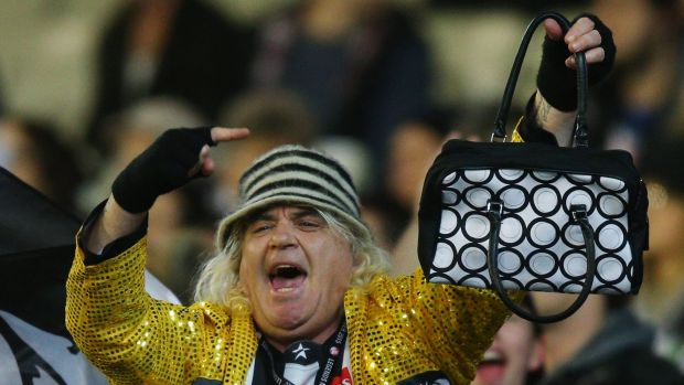 Magpies cheer squad leader Joffa Corfe adds insult to injury, holding up a handbag to Cats fans.
