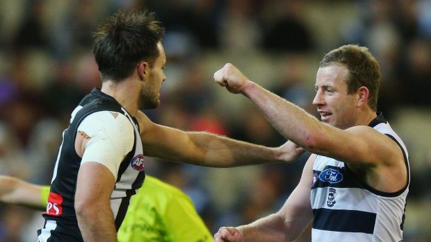 Nathan Brown of the Magpies and Steve Johnson of the Cats take a swing at each other.
