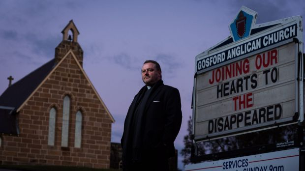 Anglican priest Father Rod Bower with the sign in front of his Gosford church which frequently features messages ...