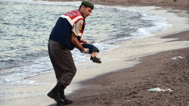 A police officer carries the body of Aylan Kurdi after he washed up on a beach near the Turkish resort of Bodrum.