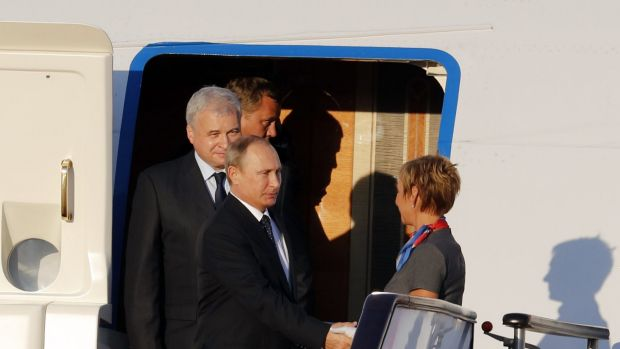 Russian President Vladimir Putin, foreground left, shakes hands with an aircrew member upon his arrival at the Beijing ...
