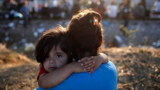 A young Syrian migrant girl is held by her mother next to railroad tracks where migrants wait to cross into Macedonia in ...