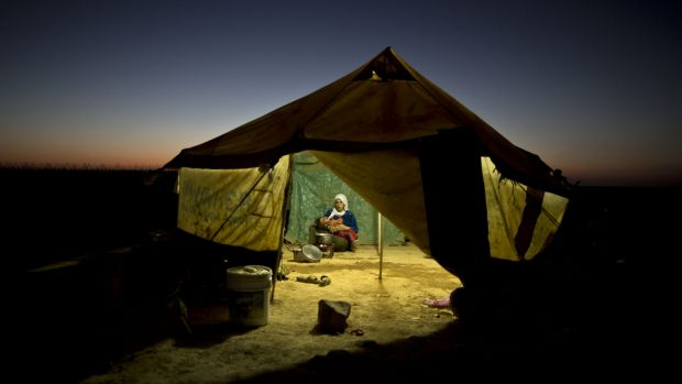A Syrian refugee tends to her daughter while cooking inside her tent at an informal tented settlement near the Syrian ...