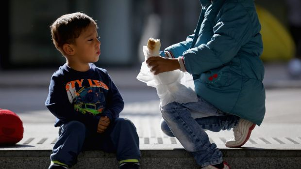 A young Syrian boy is offered food by another child as migrants wait to board a train at Keleti station in central Budapest.