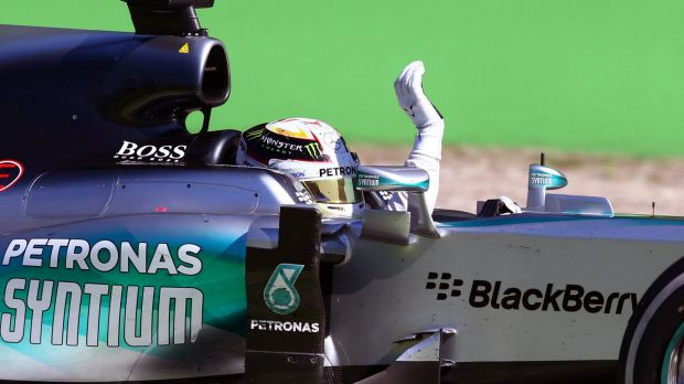 Hamilton waves to the crowd after crossing the finish line.