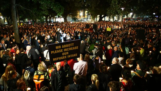 People hold candles and signs up in support of refugees in Sydney on Monday.