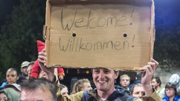 Crowds welcome refugees at the train station in Saalfeld, central Germany. Hundreds of refugees arrived by train from ...