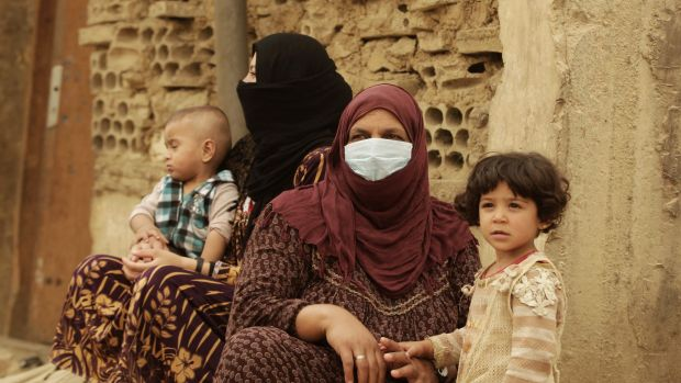 Syrian refugees cover their faces  during a sandstorm in a refugee camp in Lebanon.