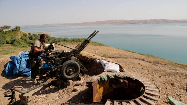 A Kurdish peshmerga prepares his weapon at his combat position on the shores of the Mosul dam.