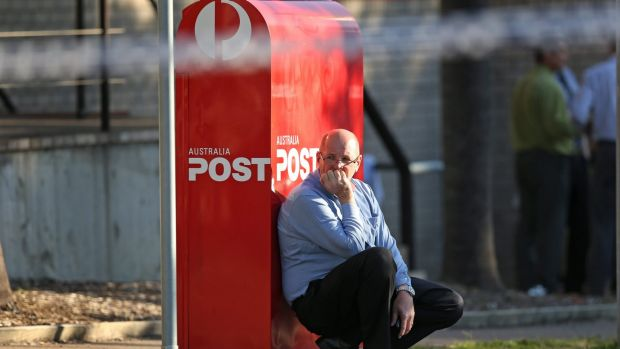 A man leans against an Australia Post letterbox at the scene of a shooting outside Warners Bay Post office on Wednesday ...
