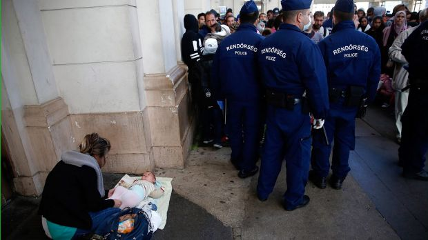 A Syrian woman changes her baby's diaper next to a line of Hungarian police at Keleti train station.