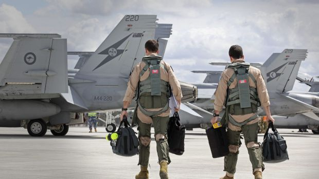 In this handout image provided by Commonwealth of Australia, F/A-18F Super Hornet aircrew head to their aircraft in ...