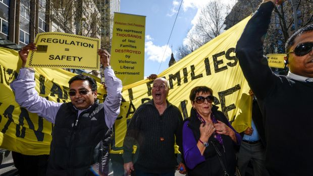 """The words """"& hire car"""" were painted by hand onto the banner, which reads """"Victorian taxi families want justice""""."""