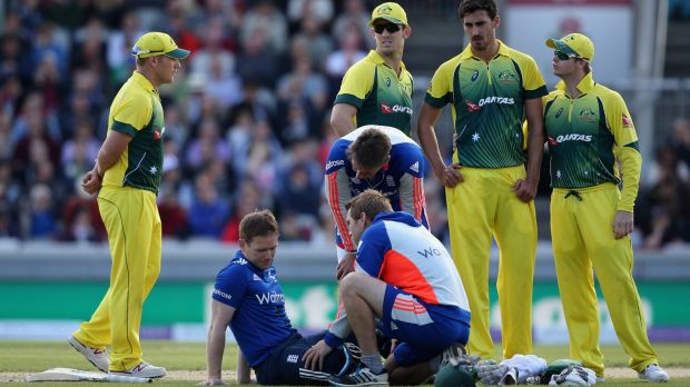 Morgan receives treatment after being struck on the helmet by a short ball from Mitchell Starc.