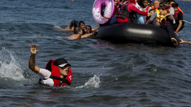 A Syrian man swims in front of a dinghy full of refugees.