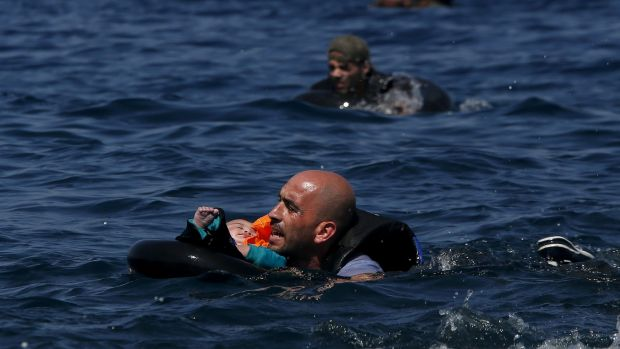 A Syrian father holding a baby in a lifetube swims towards the shore after their dinghy deflated some 100m away before ...