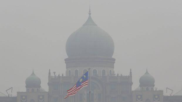 A Malaysian flag flutters in front of the prime minister's office shrouded in haze in Putrajaya, Malaysia, at the weekend.