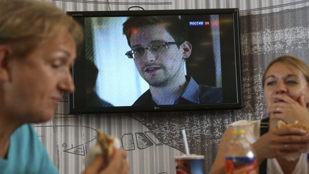 Customers eat at a cafe in Sheremetyevo airport in Moscow as a TV in the background shows an interview with Edward Snowden.