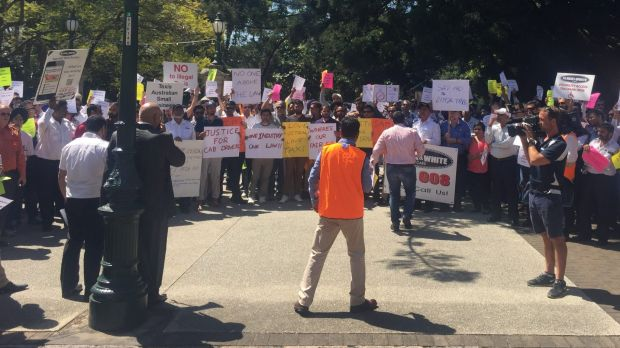 """Taxi drivers protest """"illegal taxi services"""" outside Parliament in Brisbane."""