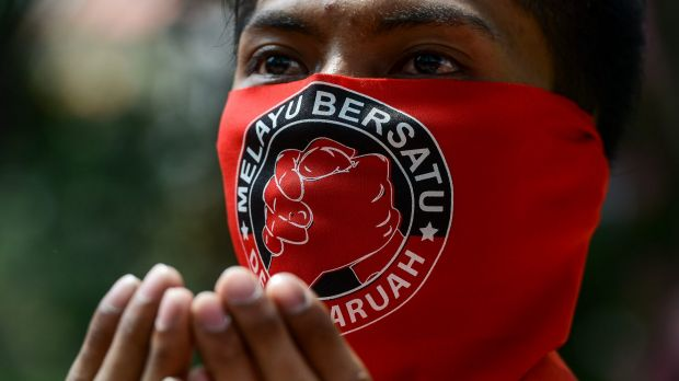 """A pro-government 'red-shirt' protester with a face mask which reads """"Malays United"""" in Kuala Lumpur."""