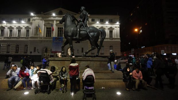 Residents sit in Santiago's main square after a powerful earthquake hit Chile's northern coast causing buildings to sway ...