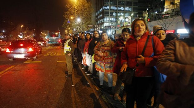 A police officer stands in the street to flag down buses to take people home after a powerful earthquake hit Chile's ...