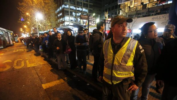 A police officer stands in the street to direct traffic as people stand in a line for public transportation after the ...