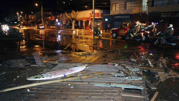 Police patrol a debris strewn street in Valparaiso, Chile, after a tsunami, caused by the earthquake.