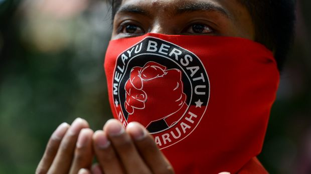 """A pro-government 'red shirt' protestor prays with a face mask which reads read """" Malay United"""" on the face, at a ..."""