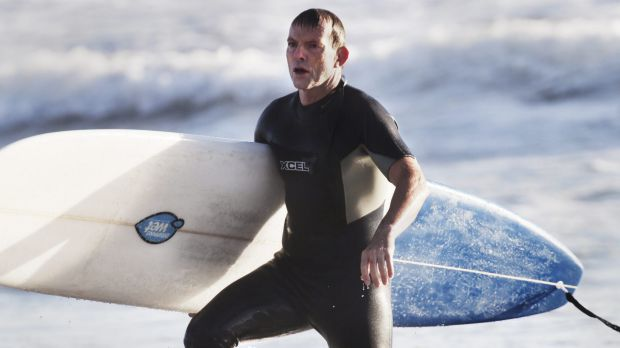 """Tony Abbott, pictured surfing in 2014, went to hospital for a """"couple of stitches"""" after encountering rough surf ..."""
