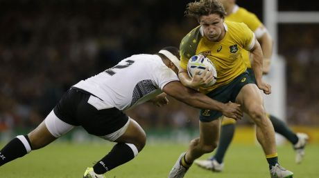 Australia's Michael Hooper is tackled by Fiji's Talemaitoga Tuapati.