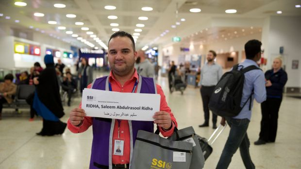 "Adam Bujairami, a ""welcome-to-Australia"" official, awaits the Ridha family, from Iraq, at Sydney International Airport."