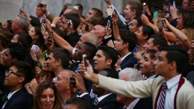 People raise their phones and cameras as Pope Francis passes.