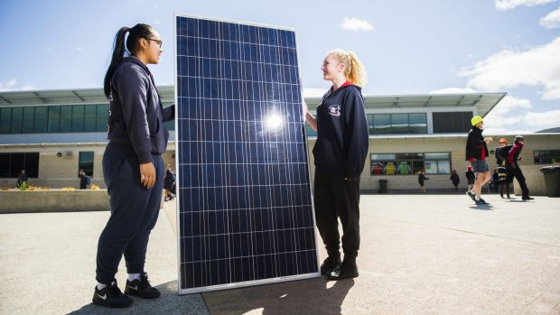 Amaroo year 10 students Savannah Sithideth and Taylah Rattey with one of the solar panels to be installed at the school.