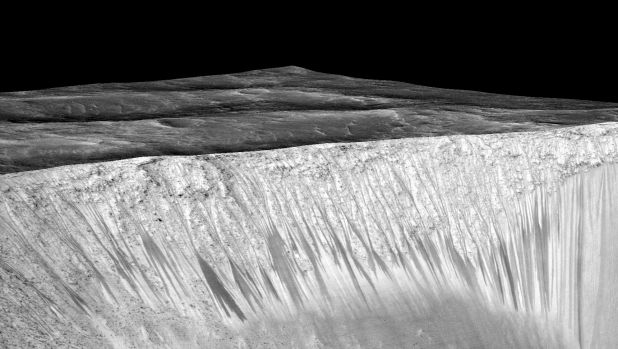 The 'recurring slope lineae' emanating out of the walls of Garni crater on Mars. NASA says the dark streaks are evidence ...