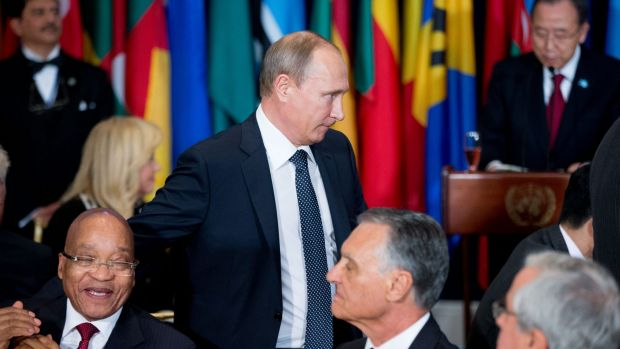 Russian President Vladimir Putin arrives for a lunch hosted by United Nations Secretary-General Ban Ki-moon, right, on ...