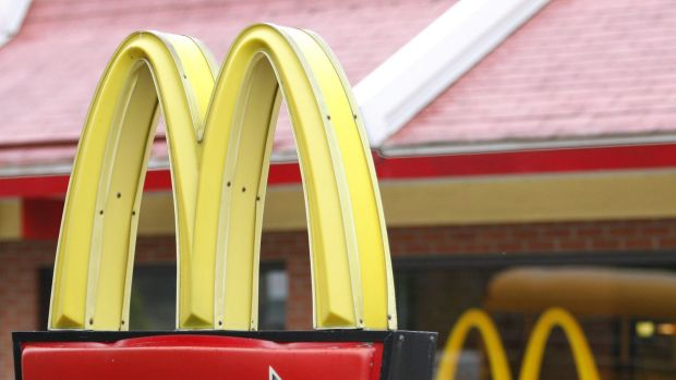 A man has been charged after allegedly spitting in the face of a young McDonald's drive-through worker.