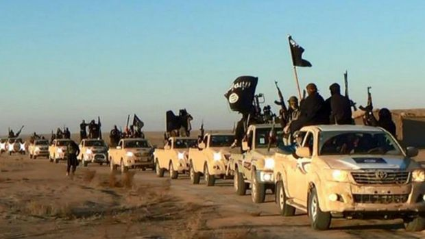 Islamic State jihadists hold up their weapons and wave flags from their vehicles in a convoy near Raqqa city in Syria, ...