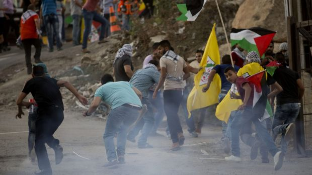 Palestinians run from tear gas during clashes with Israeli security forces at the Hizme checkpoint near the West Bank ...