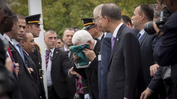 Palestine President Mahmoud Abbas kisses the flag of Palestine before it was raised at the UN for the first time on ...