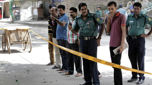 Members of Bangladeshi police stand by the site where Italian citizen Cesare Tavella was gunned down by unidentified ...