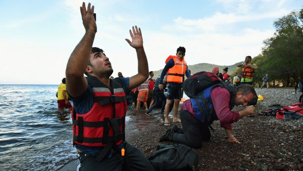 Scenes from a crisis: Men overwhelmed with emotion collapse onto the shore, praying moments after arriving on the Greek ...