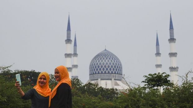 Malaysians front of the Sultan Salahuddin Abdul Aziz Shah Mosque, also known as the Blue Mosque, slightly obscured by ...