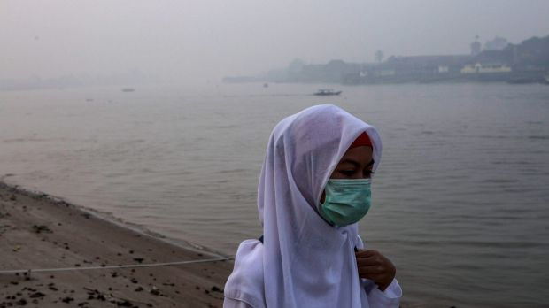 A student wears a face mask as she walks to school in Palembang, South Sumatra, Indonesia.