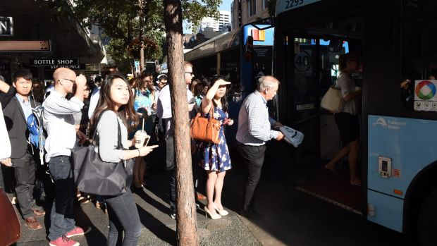 Commuters board a bus  at the Park and Elizabeth streets corner, which is said to have improved under the changes.