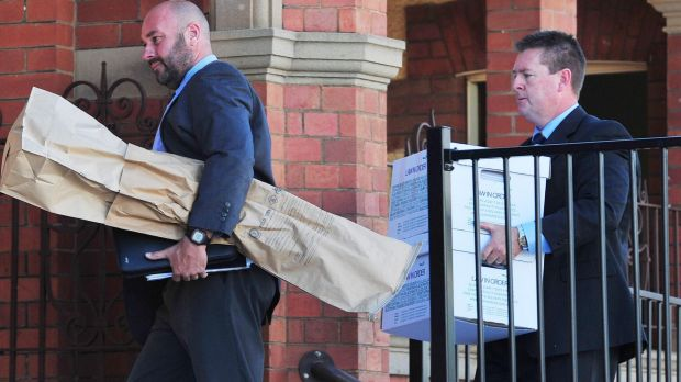 Detective Senior Constable John Cosgrove and Detective Sergeant Darren Gunn carry evidence into the Wagga courthouse, ...
