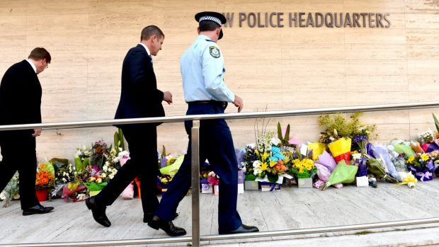 Premier Mike Baird walks past the many floral tributes left for  NSW Police accountant Curtis Cheng outside Parramatta ...