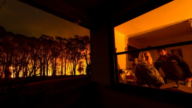 Adam Watkins and partner Prue Mathiesen in their kitchen taking a break after fighting a bushfire that threatened their ...