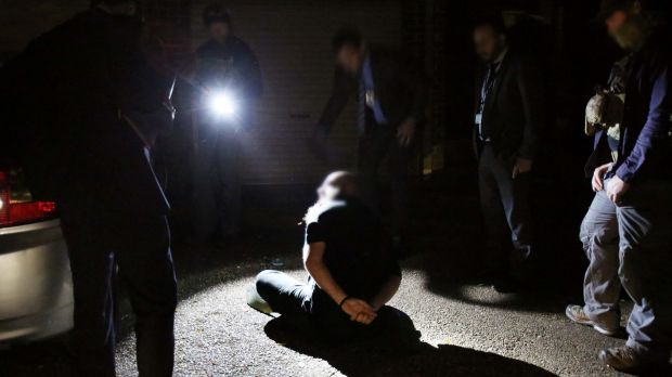 A man is arrested during the operation on Tuesday.